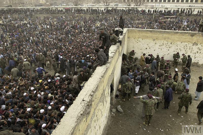 A football match between a local team, Kabul United and ISAF is watched by 30,000 spectators at the Olympic Stadium in Kabul, 15 February 2002. The match was the first international sporting event to take place in Afghanistan in five years. The Taliban regime had used the stadium for public executions. Thousands of Afghan spectators pour into the stadium for the match, 15 February 2002. Austrian and British soldiers (the latter from 2 Parachute Regiment) attempt to keep order.