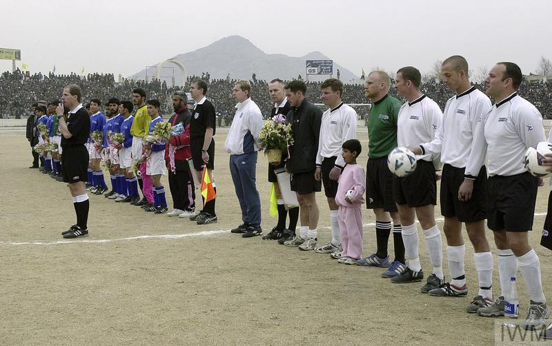 A football match between a local team, Kabul United and ISAF is watched by 30,000 spectators at the Olympic Stadium in Kabul, 15 February 2002. The match was the first international sporting event to take place in Afghanistan in five years. The Taliban regime had used the stadium for public executions. The teams from ISAF (foreground) and Kabul United line up with match officials before the start of the friendly match.