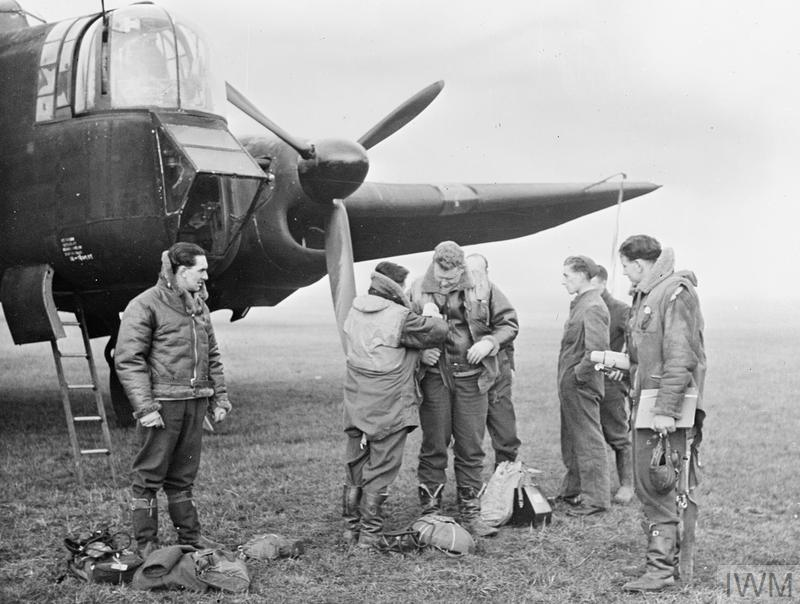 A Whitley crew preparing for a night sortie in November 1941. The ground crew wait patiently as last-minute adjustments are made to the pilot's flying clothing at dispersal. Note the parachutes and map bags on the ground, and the thermos flask- an essential item of personal kit for a seven-hour flight a draughty Whitley.