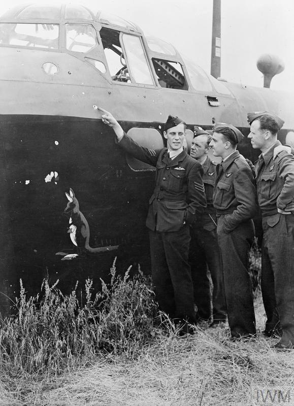 Sergeant Frank Griggs of 214 Squadron, points to some minor damage to his Stirling, N3751/BU-P, after crash-landing at Stradishall, 28 June 1942. The aircraft was damaged by flak and fighters after attacking Bremen.