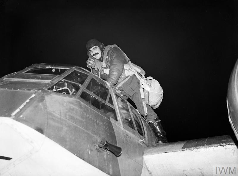 Pilot Officer Peter Kells, the pilot of a Blenheim IF of No. 29 Squadron, climbs into his cockpit at the start of another night patrol from Coleby Grange, Lincolnshire, October 1940.