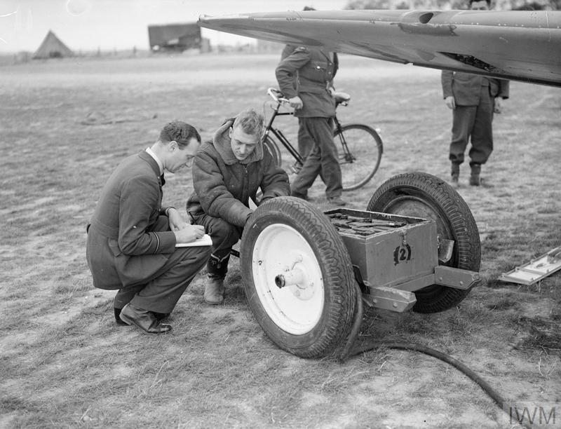 Sergeant Jennings seated on a battery cart while being debriefed by No. 19 Squadron's Intelligence Officer.