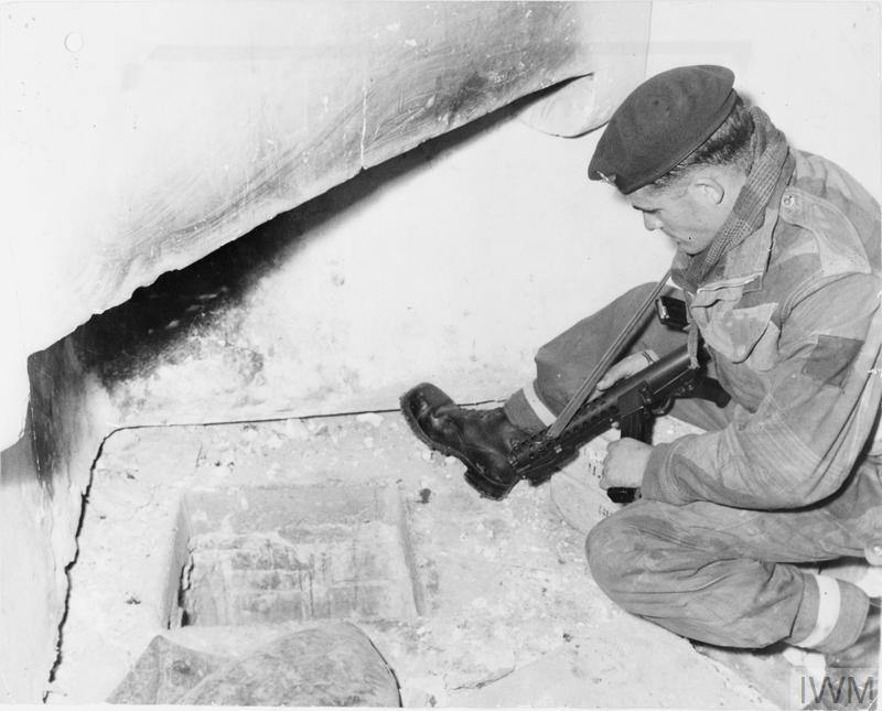 Operation Black Mac: Corporal Tom Westcott of the 2nd Battalion, Parachute Regiment, looking at the opening in the floor of a kitchen in a mountain village house, which led to an underground room where six terrorists were hiding.