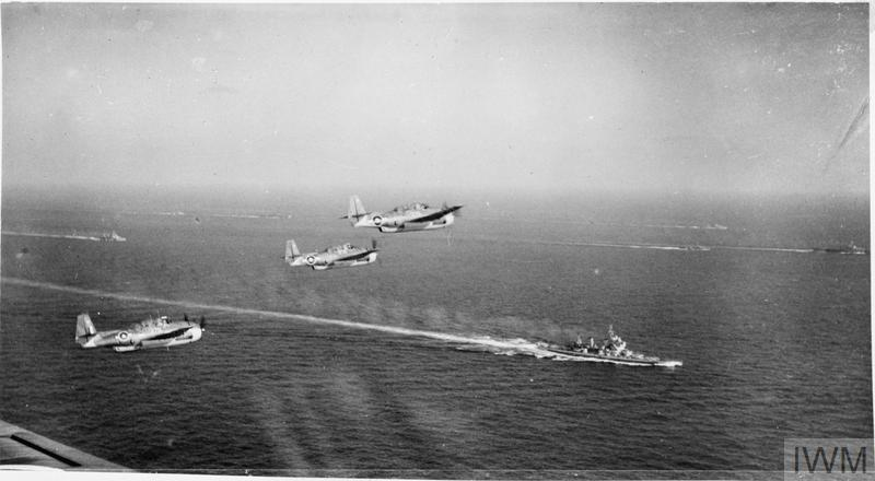 Three Grumman Avengers flying over the battleship HMS KING GEORGE V and other units of the British Pacific Fleet when on the way to attack Sakishima targets in support of the American landing on Okinawa.