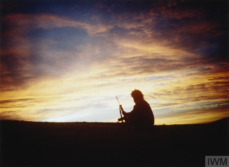 A soldier of 3rd Battalion, the Parachute Regiment silhouetted against the sunset at Windy Gap, East Falkland.