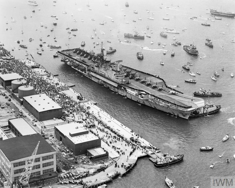 Aerial view of the aircraft carrier HMS HERMES about to berth alongside at Portsmouth Harbour on her return from the Falklands on 21 July 1982. HERMES is surrounded by small boats which sailed out to welcome her home. Crowds can also be seen on the quayside.