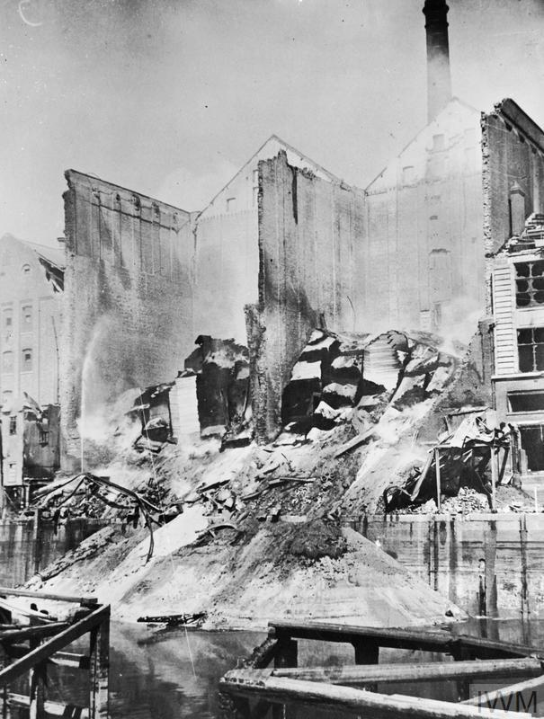 Smouldering grain cascades slide into the river at Hull after the raid on the night of 7/9 May 1941.
