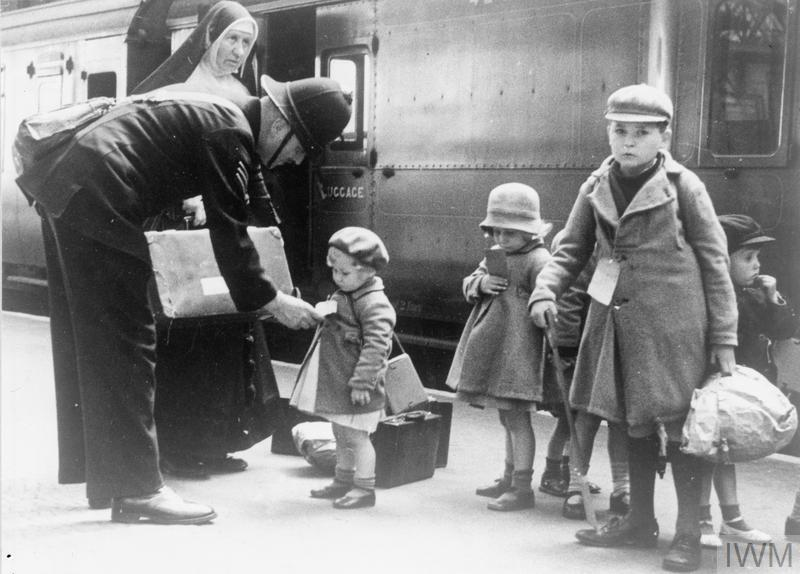 A policeman helps some young evacuees, and a nun who is escorting them, at a London station