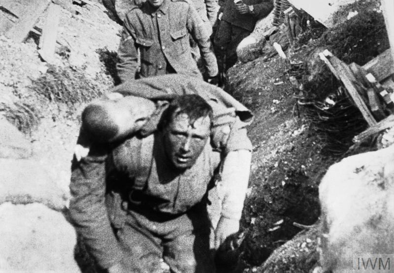"Still from the British film ""The Battle of the Somme"". The image is part of a sequence introduced by a caption reading ""British Tommies rescuing a comrade under shell fire. (This man died 30 minutes after reaching the trenches)"". The scene is generally accepted as having been filmed on the first day of the Battle of the Somme, 1 July 1916."