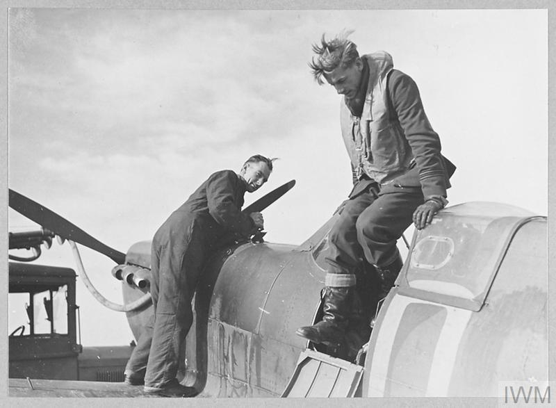 Flight Lieutenant C A T (Cyril Arthur Trevor) Jones of No. 616 Squadron climbs out of his Spitfire (QJ-A) while a member of the ground staff refuels the aircraft, Fowlmere, September 1940.