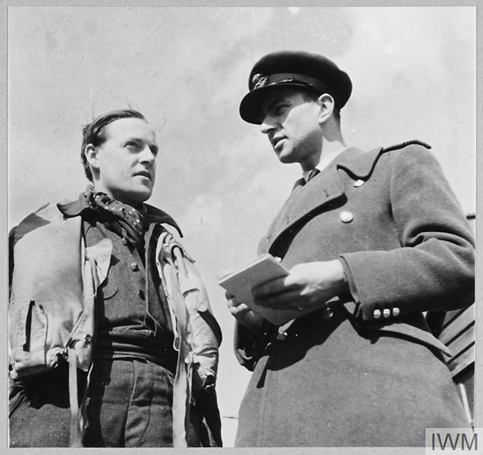 Squadron Leader P M Brothers (left) Commanding Officer of No. 457 Squadron RAAF, describing a sweep over northern France to the Squadron Intelligence Officer at Redhill, Surrey.