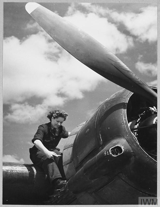 A flight mechanic of the W.A.A.F services a Bristol Beaufighter