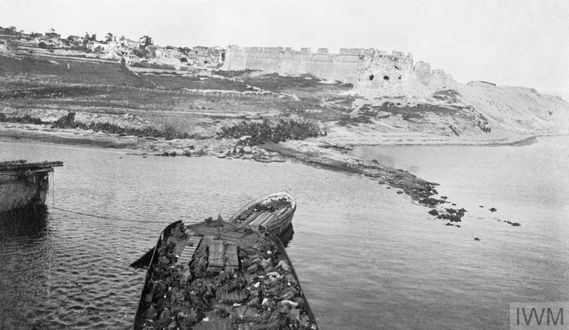 Sedd el Bahr fort photographed from the SS RIVER CLYDE. A party of Dublin Fusiliers are sheltering on land, and wounded men of the Munster Fusiliers are lying on board a lighter in the foreground.