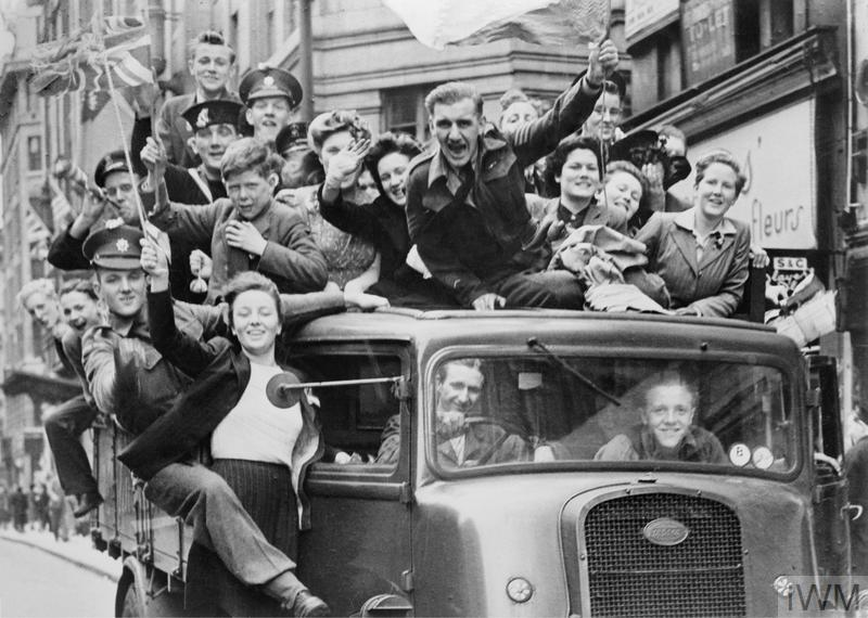 A truck of revellers passing through the Strand, London, 8 May 1945.