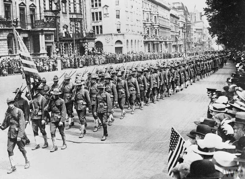 American troops parade with the Stars and Stripes carried in front down Piccadilly in London.