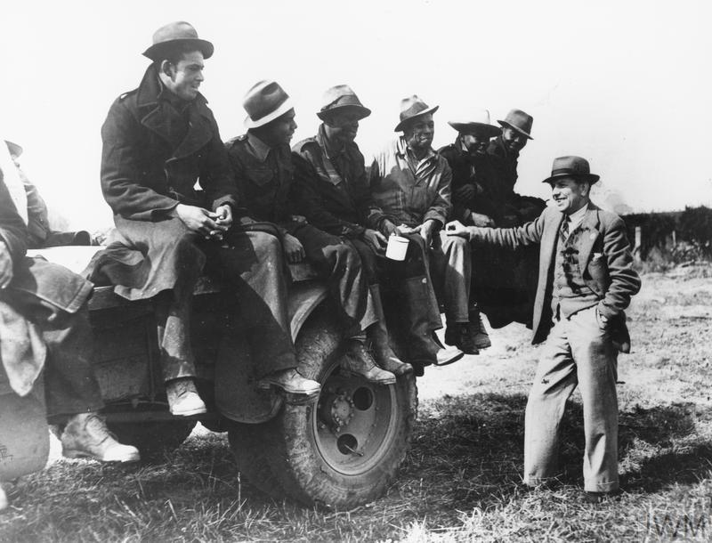 West Indian Labour Force in Britain: A group of British Honduran Forestry workers, finished work for the day on the pine clad hills of East Lothian, Scotland, are seen talking to the manager Mr John Dunbar. Forestry workers, left to right: Aldrick Garbutt, A Thomas, W Ellis, A Smith, E Arane and B Augustine.