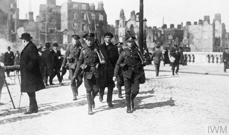 Guarded by British troops, an arrested Irish republican is marched across a bridge following the Easter Rising in Dublin in April 1916.