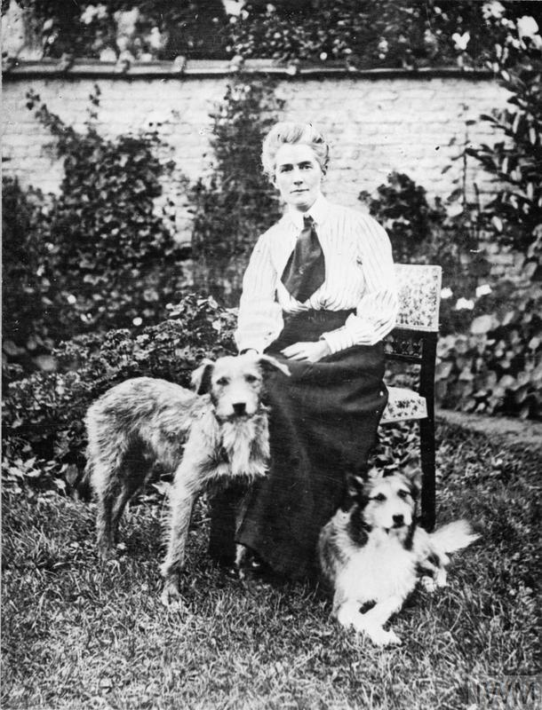 "Pre-War Life in Brussels - A portrait of nurse Edith Cavell as she sits in a garden her two dogs. The dog on the right, ""Jack"" was rescued after her execution."