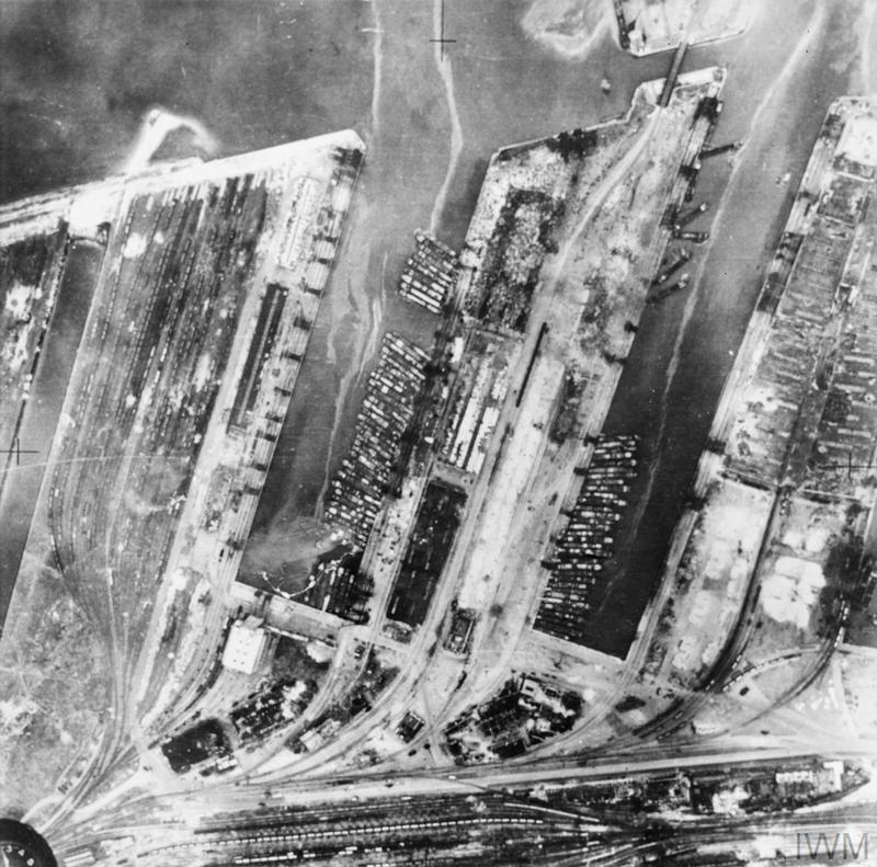 Vertical aerial photograph taken from 3,100 feet by Bristol Blenheim Mark IV, T2032, of No. 82 Squadron RAF, of part of the docks at Dunkirk. Invasion barges assembled for Operation SEALION are moored to Mole No. 4 in the Bassins de Freycinet. A number of sunk and damaged barges can be seen at the top of Darse No. 4, and the dock buildings to its right are completely destroyed. Two of the three warehouses on Mole No. 4 have been gutted by fire and wharves.