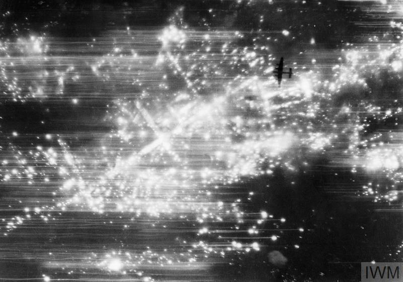 Vertical photograph taken from 19,000 feet during a night raid on Hannover, showing an Avro Lancaster, silhouetted by the many incendiary fires below, flying due south over the Sudstadt district. The main thoroughfare, picked out by incendiaries and running from lower left to upper right, is the northern end of Sallstrasse. 3,932 buildings were totally destroyed, and more than 30,000 damaged in varying degree, by the intense conflagration in the central and south central districts of the city resulting from