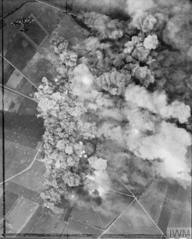 An Avro Lancaster leaves the target area (top left), as smoke from exploding bombs smothers the village of Cagny, south-east of Caen, France. 942 aircraft of Bomber Command were despatched to bomb German-held positions, in support of the Second Army attack in the Normandy battle area (Operation GOODWOOD), on the morning of 18 July 1944.